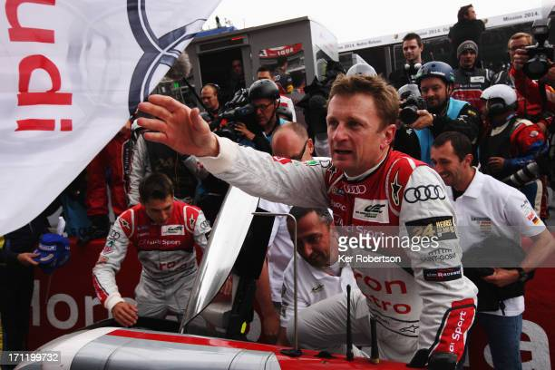 Allan McNish of Great Britain celebrates as he and his fellow Audi Sport Team etron quattro codrivers Tom Kristensen of Denmark and Loic Duval of...