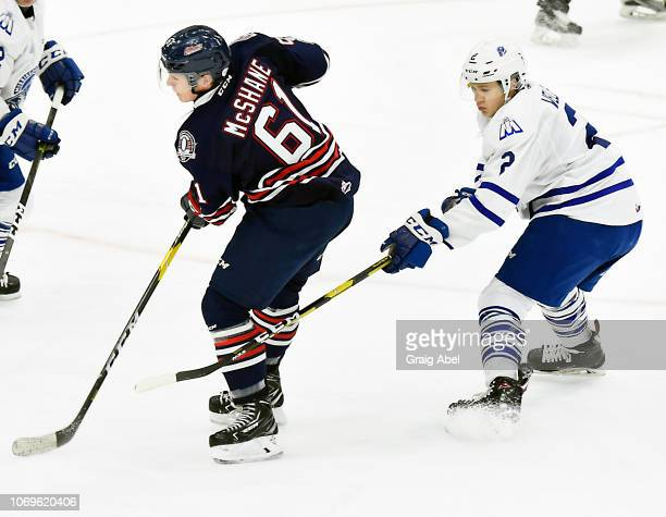 Allan McShane of the Oshawa Generals controls the puck against Ryan Wells of the Mississauga Steelheads during OHL game action on December 7 2018 at...
