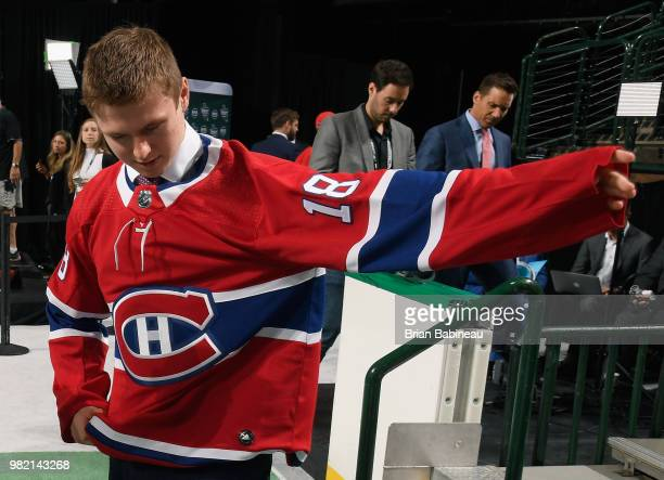 Allan McShane puts on hs jersey after being selected 97th overall by the Montreal Canadiens during the 2018 NHL Draft at American Airlines Center on...