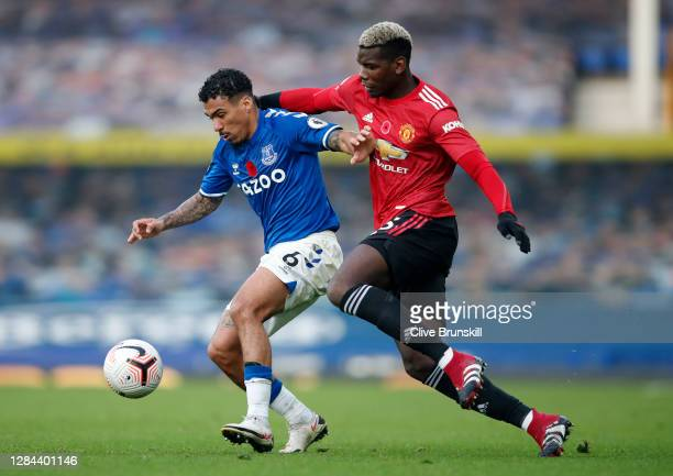 Allan of Everton is challenged by Paul Pogba of Manchester United during the Premier League match between Everton and Manchester United at Goodison...
