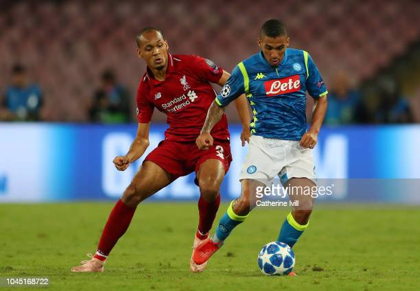 Allan of Napoli passes the ball under pressure from Fabinho of Liverpool during the Group C match of the UEFA Champions League between SSC Napoli and...