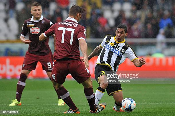 Allan of Udinese Calcio tackles Panagiotis Tachtsidis of Torino FC during the Serie A match between Torino FC and Udinese Calcio at Stadio Olimpico...