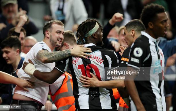 Allan Saint-Maximin of Newcastle United celebrates with a fan after scoring their team's first goal during the Premier League match between Newcastle...