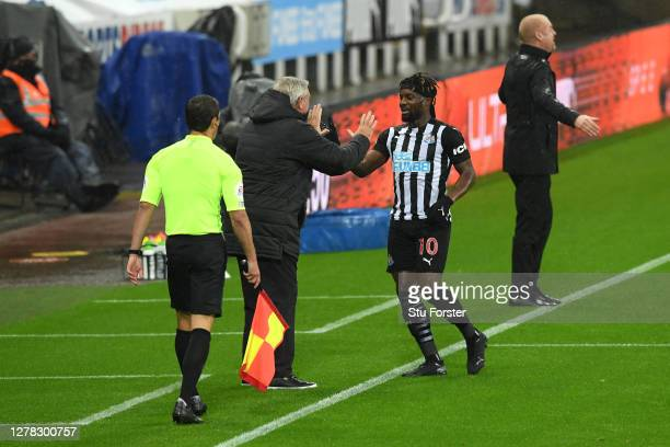 Allan Saint-Maximin of Newcastle United celebrates with Steve Bruce, Manager of Newcastle United after scoring his team's first goal during the...