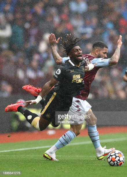 Allan Saint-Maximin of Newcastle United is challenged by Douglas Luiz of Aston Villa during the Premier League match between Aston Villa and...