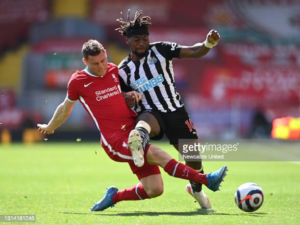 Allan Saint-Maximin of Newcastle United is tackled by James Milner of Liverpool during the Premier League match between Liverpool and Newcastle...