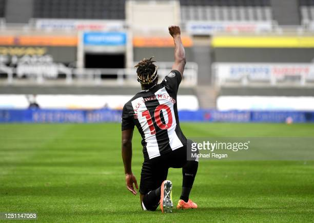 Allan Saint-Maximin of Newcastle United takes a knee as he celebrates after scoring his sides first goal during the Premier League match between...