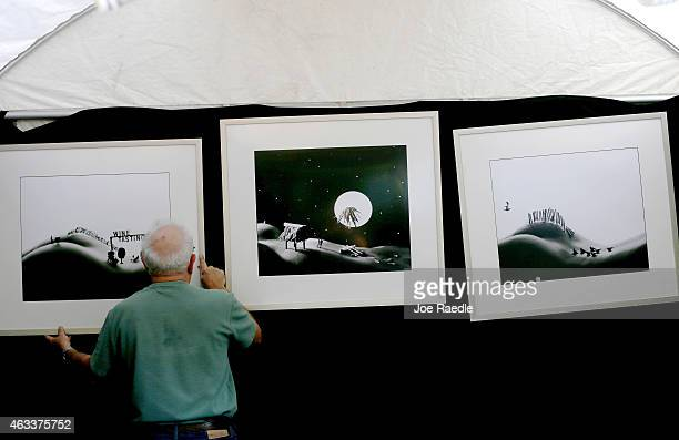 Allan Teger puts his'Bodyscapes' photographs on display for the opening of the 52nd Annual Coconut Grove Arts Festival on February 13 2015 in Miami...