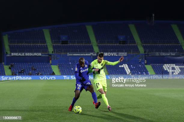 Allan-Romeo Nyom of Getafe CF battles for possession with Yannick Ferreira Carrasco of Atletico Madrid in front of empty stands during the La Liga...