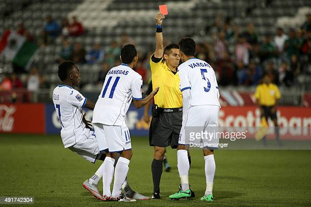 Allans Vargas of Honduras is given a red card by referee Armando Villareal in the second minute against Mexico as teammates Allan Banegas and Alberth...