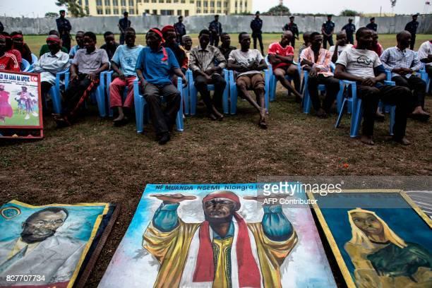 Alleged attackers sit behing paintings of Bundu Dia Mayala group leader Muanda Nsemiare on display at police headquarters in Kinshasa on August 8 a...