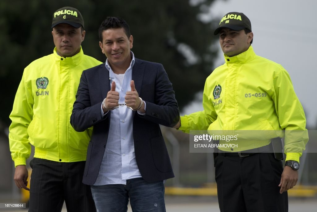 Alleged drug-trafficker Camilo Torres, a.k.a. 'Fritanga', gives the thumbs up as he is escorted by Colombian policemen to board a plane during his extradition to the United States at an anti-narcotics police base in Bogota, Colombia, on April 25, 2013. AFP PHOTO/Eitan Abramovich