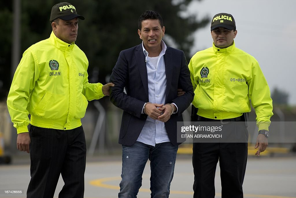 Alleged drug-trafficker Camilo Torres, a.k.a. 'Fritanga', is escorted by Colombian policemen to board a plane during his extradition to the United States at an anti-narcotics police base in Bogota, Colombia, on April 25, 2013. AFP PHOTO/Eitan Abramovich