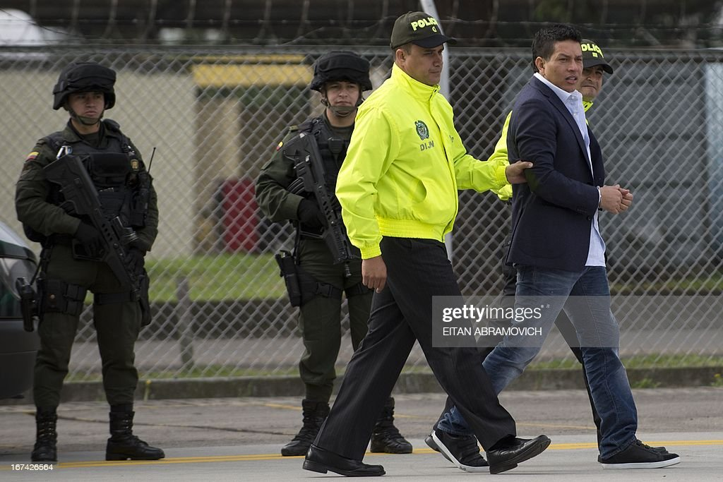 Alleged drug-trafficker Camilo Torres, a.k.a. 'Fritanga' (R), is escorted by Colombian policemen to board a plane during his extradition to the United States at an anti-narcotics police base in Bogota, Colombia, on April 25, 2013. AFP PHOTO/Eitan Abramovich