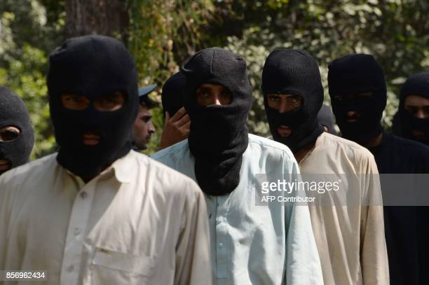 Alleged fighters for the Islamic State and Taliban walk being presented to the media at the police headquarters in Jalalabad on October 3 2017 Afghan...