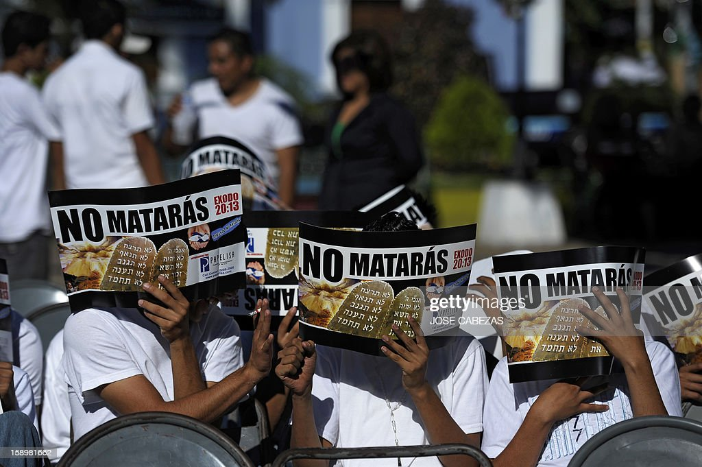 Alleged gang members cover their faces with papers reading 'You will not kill' during a religious service in Apopa, 14 km north of San Salvador, El Salvador on January 4, 2013. Raul Mijango, Gang truce mediator, announced that 18 districs in El Salvador will be considered 'Sanctuary Territories' for gangs as a second stage of the gang truce. AFP PHOTO/ Jose CABEZAS
