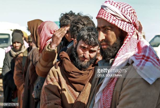 Alleged Islamic State group fighters who fled from the frontline Syrian village of Baghuz near the Iraqi border stand in a queue as they await to be...