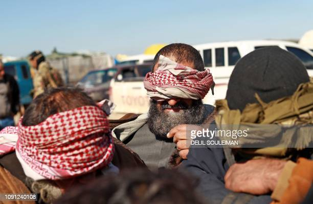 TOPSHOT Alleged Islamic State group fighters who fled from the frontline Syrian village of Baghuz near the Iraqi border sit blindfolded in the back...