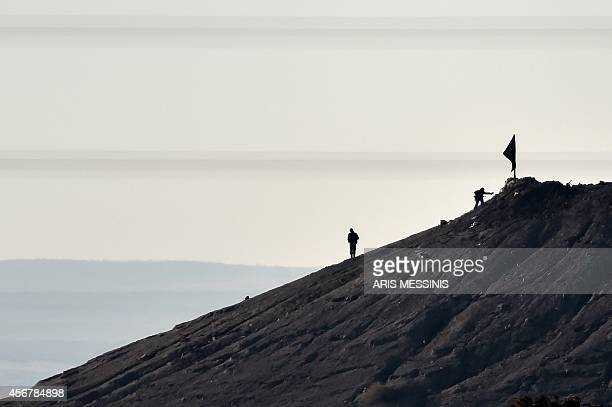 Alleged Islamic State militants stand next to a black IS flag atop a hill in at the eastern part of the Syrian town of Ain alArab known as Kobane by...