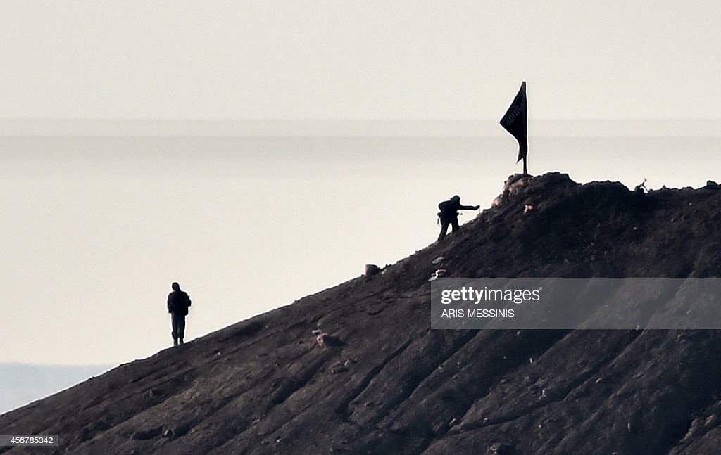 Alleged Islamic State (IS) militants stand next to a black IS flag atop a hill in at the eastern part of the Syrian town of Ain al-Arab, known as Kobane by the Kurds, as seen from the Turkish-Syrian border in the southeastern town of Suruc, Sanliurfa province, on October 7, 2014. Fresh air strikes by the US-led coalition hit positions held by Islamic State jihadists in the southwest of the key Syrian border town of Ain al-Arab (Kobane), according to an AFP journalist just across the border in Turkey. The strikes came a day after the extremists pushed into Kobane, seizing three districts in the city's east after fierce street battles with its Kurdish defenders.