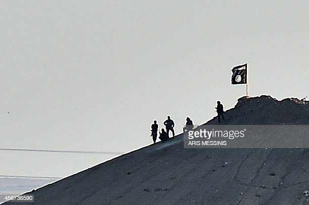 Alleged Islamic State militants stand next to an IS flag atop a hill in the Syrian town of Ain alArab known as Kobane by the Kurds as seen from the...