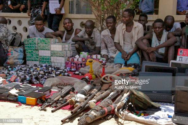 Alleged kidnappers are paraded by the police in Maiduguri on May 23, 2019 in front of confiscated goods such as weapons, medicined, phones and other...