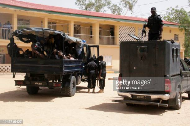 Alleged kidnappers are taken away by the police in Maiduguri on May 23 2019 after having been paraded in front of confiscated goods such as weapons...