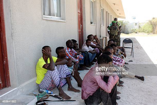 Alleged members of a local militia sit next to soldiers of the African Union's AMISOM force as they detained at the Halane military base after heavy...