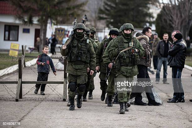 Alleged Russian soldiers in full body armor and armed with an assault rifles are marching away from the besieged Ukrainian Military Base in...