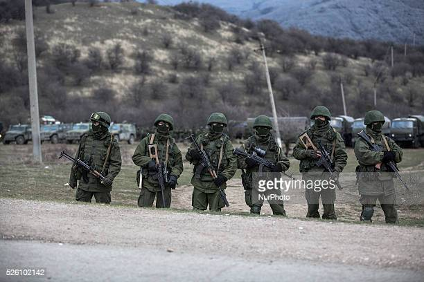 Alleged Russian soldiers in full body armor and armed with an assault rifles next to the besieged Ukrainian Military Base in Perevalnoye close to...