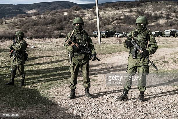 Alleged Russian soldiers in full body armor and armed with assault rifles standing in front of the besieged Ukrainian Military Base in Perevalnoye...