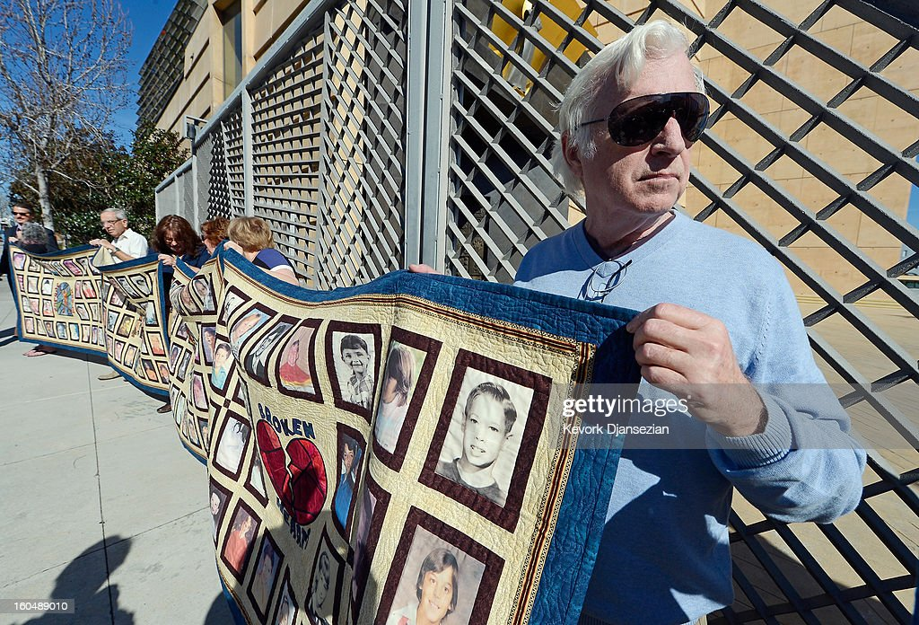 Alleged sexual abuse victim Jim Robertson (R) holds up a quilt with pictures of other alleged victims of sexual abuse by priests in the Catholic Archdiocese of Los Angeles during a news conference urging victims to come forward on February 1, 2013 at Cathedral of Our Lady of the Angels in Los Angeles, California. Retired Cardinal Roger Mahony of Catholic Archdiocese of Los Angeles, who avoided criminal charges over the way he handled pedophile priests during his career, was reportedly stripped of his archdiocese duties February 1, by his successor Archbishop Jose Gomez.
