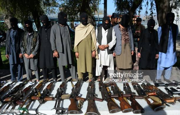 Alleged Taliban fighters and other militants stand handcuffed while being presented to the media at a police headquarters in Jalalabad on March 6...