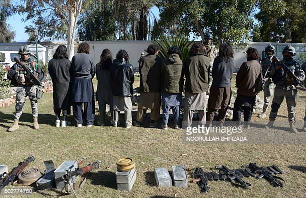 Alleged Taliban militants stand handcuffed near seized weapons while being presented to the media in Jalalabad Nangarhar province on December 29 2015...
