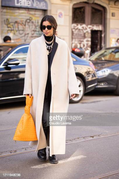 Allegra Benini wearing a long cream coat orange bag and black boots is seen outside Agnona show during Milan Fashion Week Fall/Winter 20202021 on...