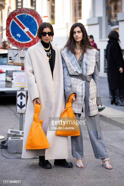 Allegra Benini wearing a long cream coat orange bag and black boots and Chiara Totire wearing a grey checked suit light grey checked vest orange bag...