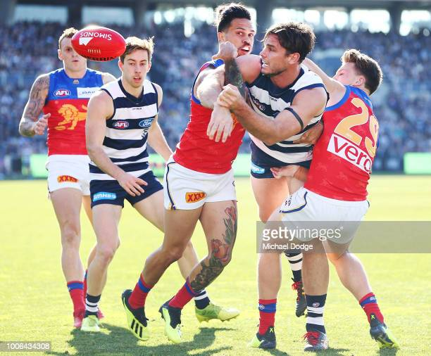Allen Christensen and Alex Witherden of the Lions tackle Tom Hawkins of the Cats during the round 19 AFL match between the Geelong Cats and the...