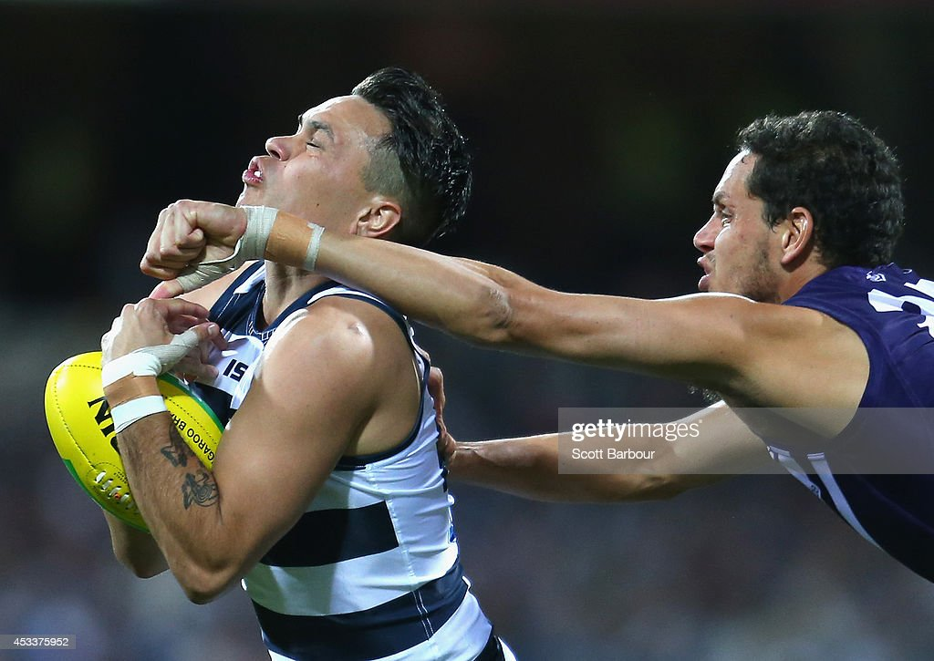 Allen Christensen of the Cats is tackled by Michael Johnson of the Dockers during the round 20 AFL match between the Geelong Cats and the Fremantle Dockers at Skilled Stadium on August 9, 2014 in Geelong, Australia.