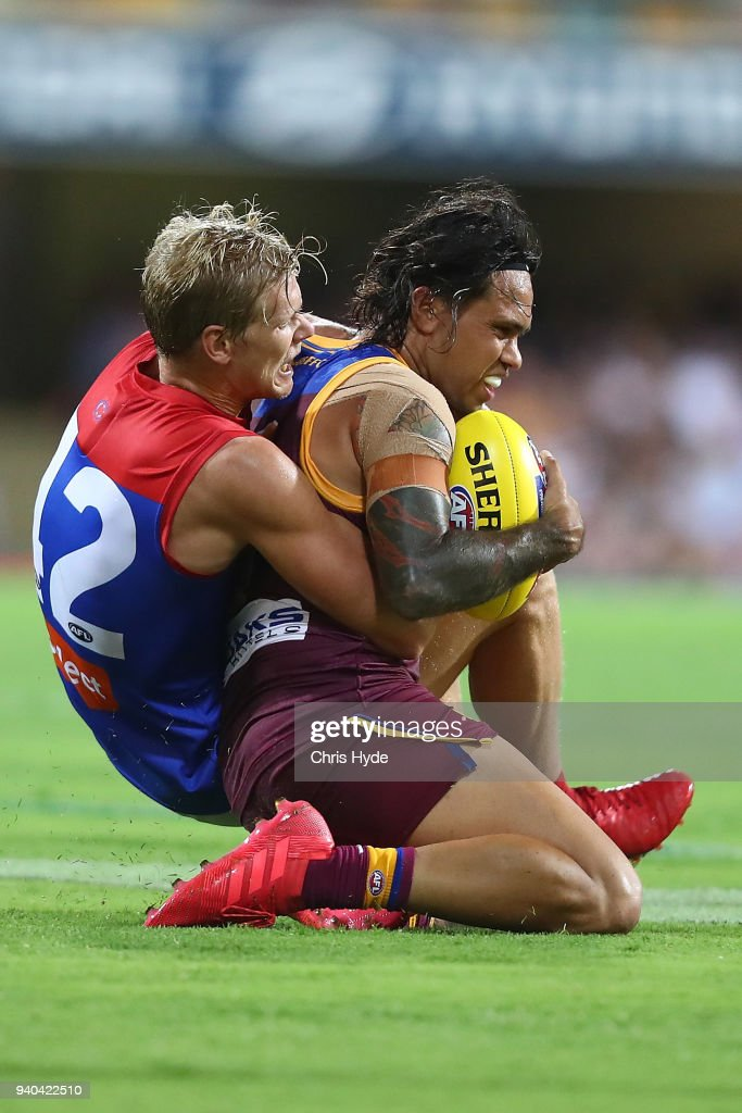 Allen Christensen of the Lions is tackled during the round two AFL match between the Brisbane Lions and the Melbourne Demons at The Gabba on March 31, 2018 in Brisbane, Australia.