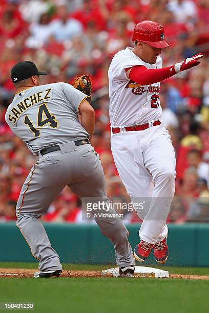 Allen Craig of the St Louis Cardinals avoids being tagged out at first base by Gaby Sanchez of the Pittsburgh Pirates at Busch Stadium on August 19...