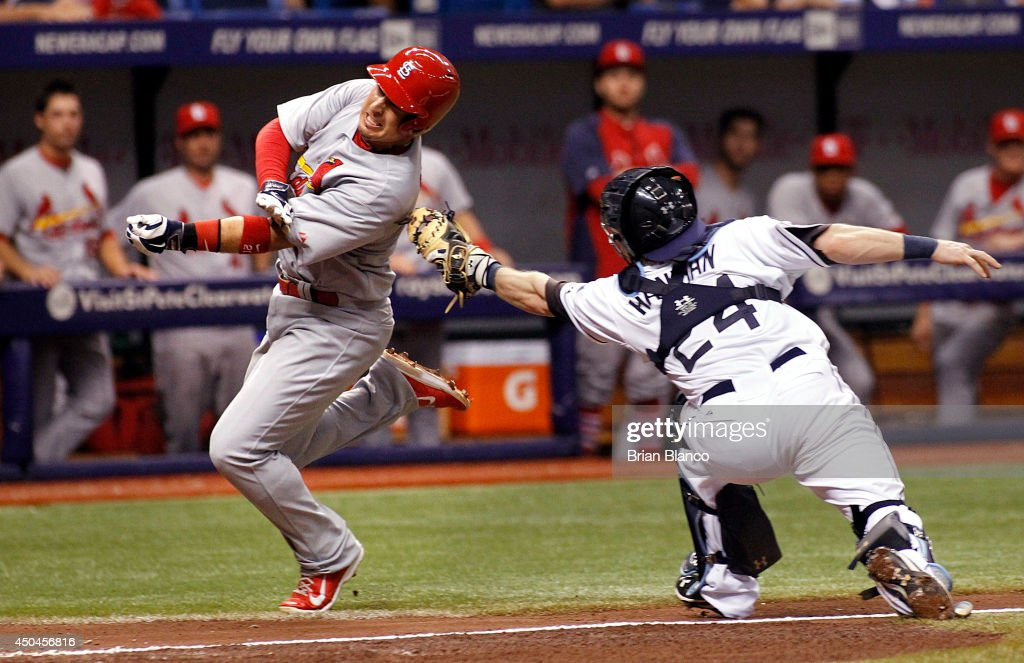 Allen Craig #21 of the St. Louis Cardinals avoids the tag by catcher Ryan Hanigan #24 of the Tampa Bay Rays as he runs home to score off of a two-run single by Yadier Molina #4 of the St. Louis Cardinals during the third inning of a game on June 11, 2014 at Tropicana Field in St. Petersburg, Florida.