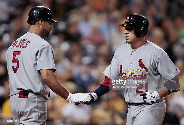 Allen Craig of the St Louis Cardinals is congratulated by teammate Albert Pujols after hitting a solo home run against the Pittsburgh Pirates during...