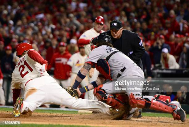 Allen Craig of the St. Louis Cardinals slides into home with the winning run despite a tag by Jarrod Saltalamacchia of the Boston Red Sox in the...