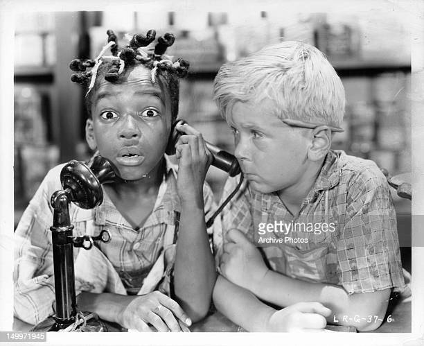 Allen 'Farina' Hoskins on phone with Jackie Cooper watching in a scene from unidentified 'Our Gang' comedy circa 1930