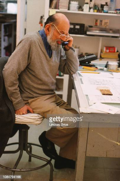 Allen Ginsberg talks on the telephone while seated at the drafting table as he works in studio at Gemini G.E.L. Preparing his Buddhist drawings for a...