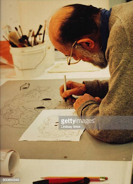 Allen Ginsberg talks on the telephone while seated at the drafting table as he works in studio at Gemini GEL preparing his Buddhist drawings for a...