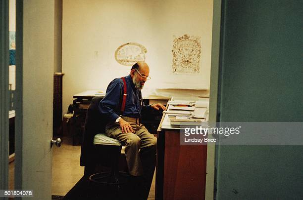 Allen Ginsberg viewed through doorway in his studio at Gemini GEL on Melrose Avenue preparing series of Buddhist drawings for series of lithographs...