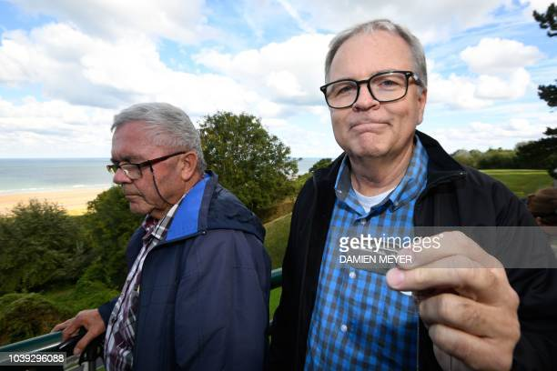 Allen Henderson of Greenville South Carolina holds his father's dog tag as he stands next to Andre Gantois a resident of Ludres in eastern France at...