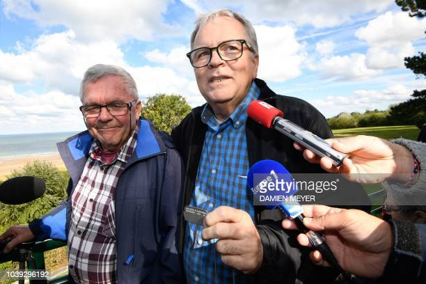 Allen Henderson of Greenville South Carolina speaks to the press as he holds his father's dog tag while standing next to Andre Gantois a resident of...