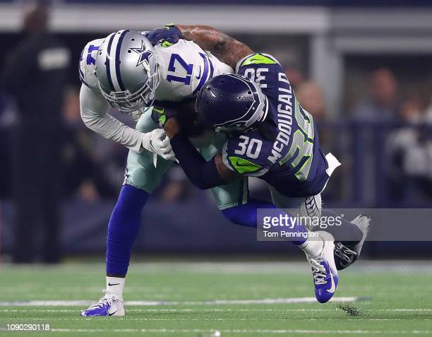 Allen Hurns of the Dallas Cowboys is tackled by Bradley McDougald of the Seattle Seahawks in the first quarter during the Wild Card Round at ATT...